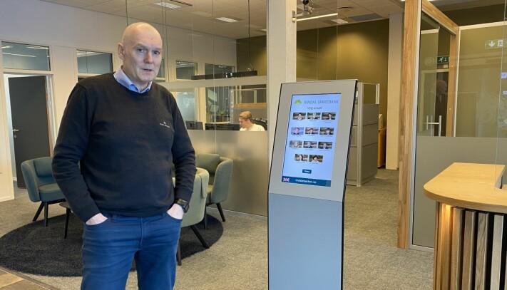 Banksjef Magne Bjørnstad ved det nye inngangspartiet. Her kan besøkende registrere seg på skjermen når de kommer.
