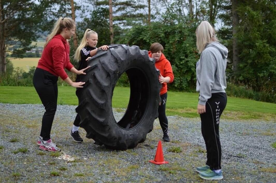 Bilde fra SkoFaden - en happening fra starten av skoleåret, da avdelingene gjennomfører forskjellige oppgaver. Her triller gruppa til Vanja et traktordekk gjennom ei løype markert med kjegler.