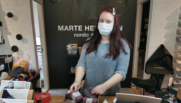 Liv Marit Kirkholt i full sving med å pakke varer som skal sendes til strikkeglade kunder