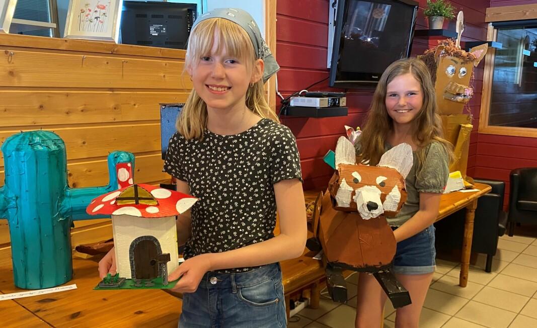 Mona og Klara med fine pappfigurer som de har laget.
