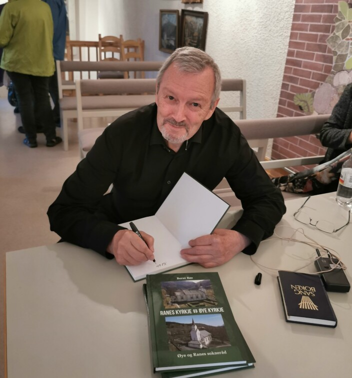 Bernt Bøe signerer boka han har skrive om dei to kyrkjene i nedre Surnadal