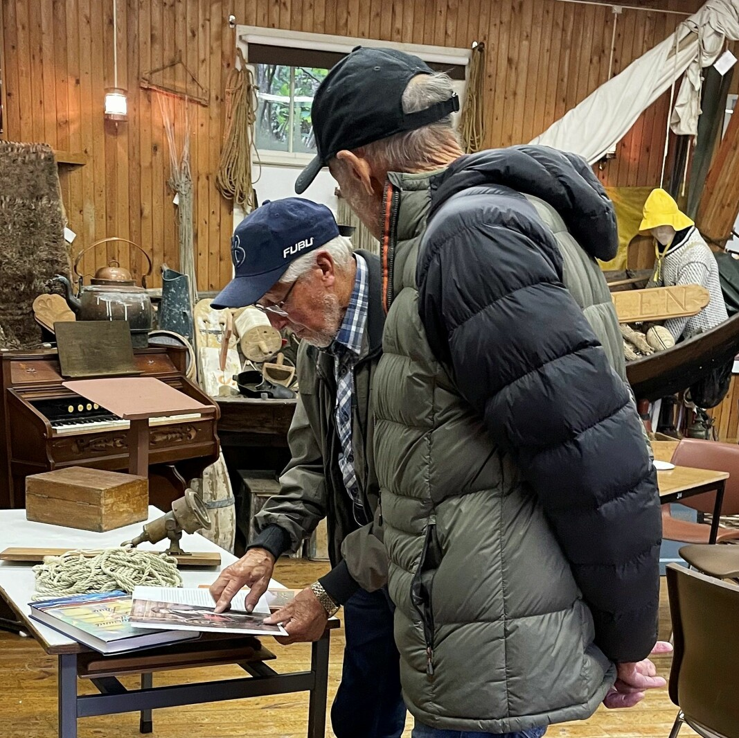 Museet byr på salg av lokal litteratur. Her blar Oddmund Gravvold og Steinar Sæterøy i husflidsboka «Nordmørssøm».