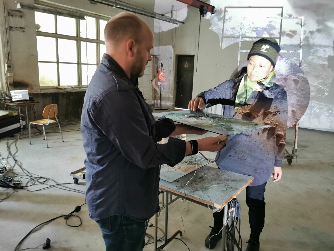 Apichaya Wanthiang tømmer pulver på platen mens Øyvind Brantsegg registrerer lyden vibtasjonene lager