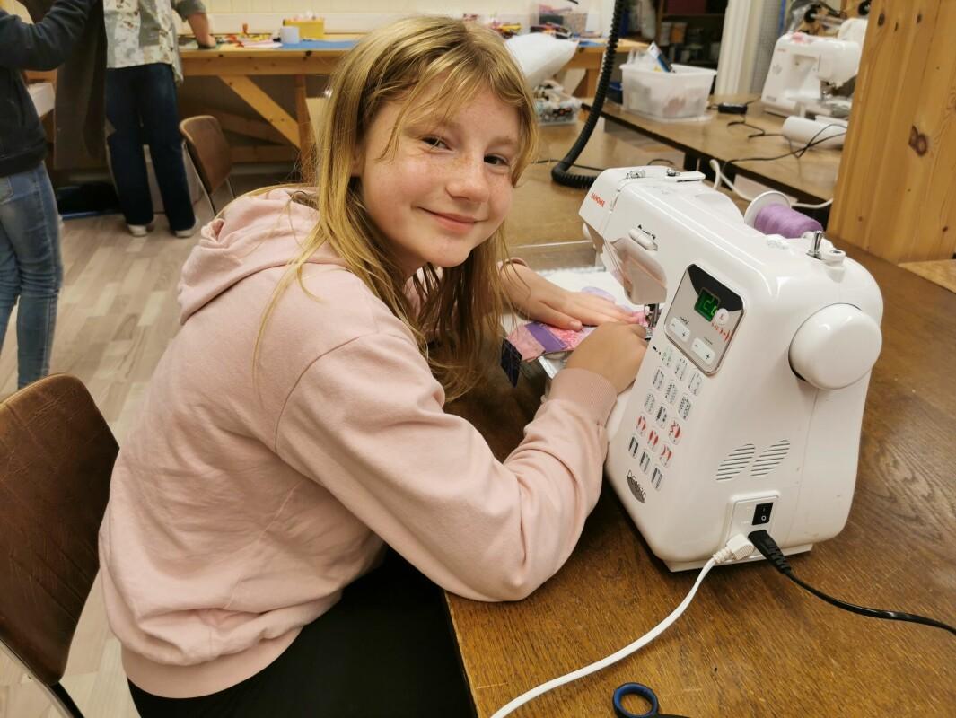 Bente Hyldbakk håndterer symaskina med et smil